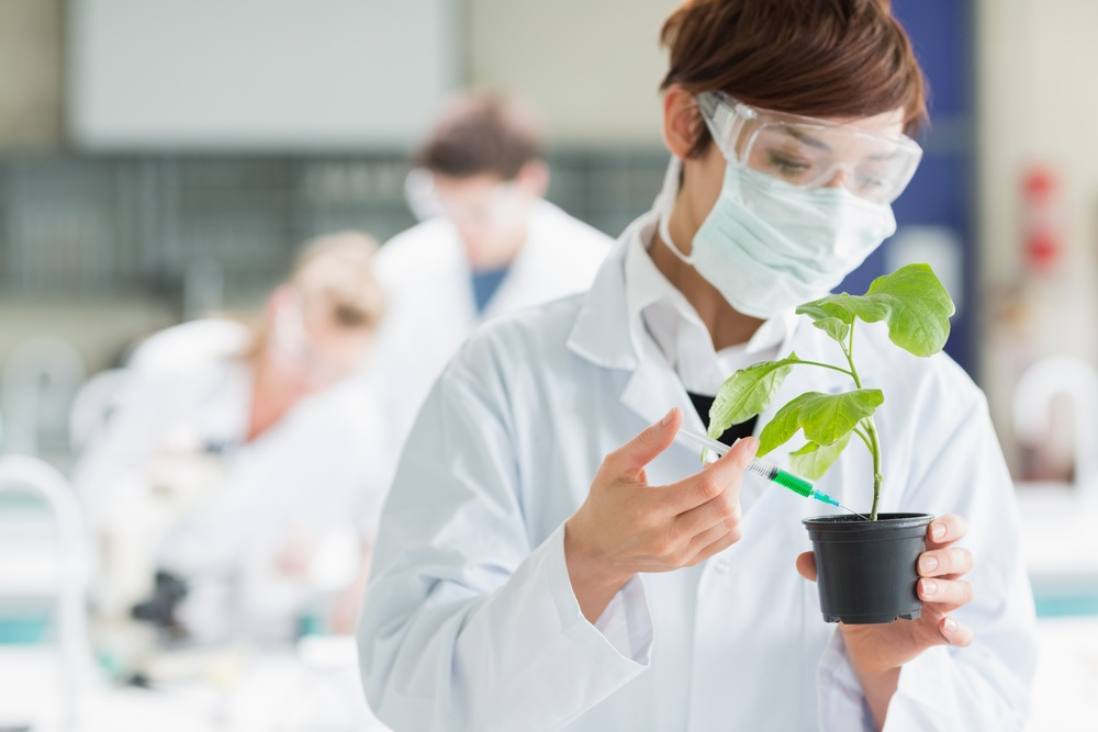 Woman standing at the laboratory while holding a plant adding chemical to soil with syringe.jpeg